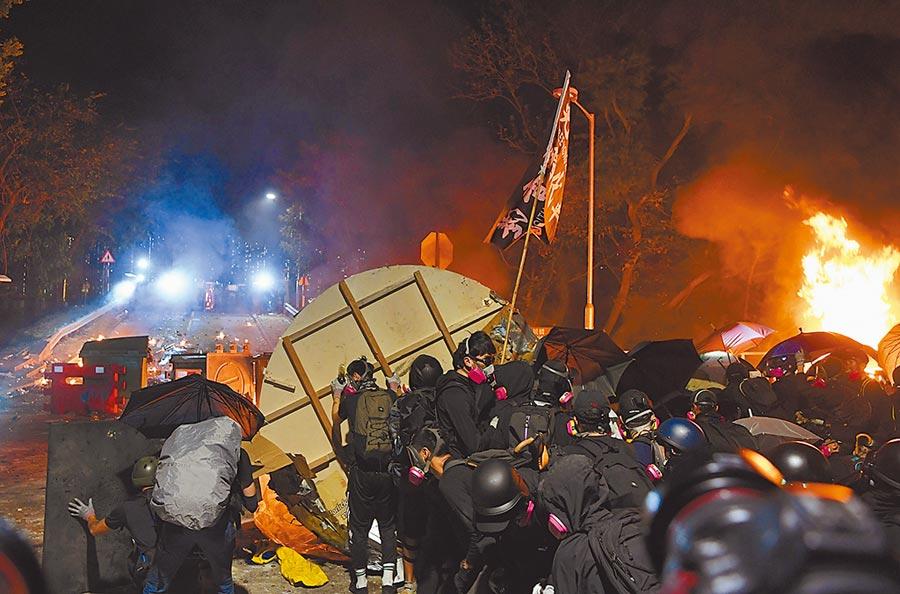 香港反送中風波爆發以來,警方首次破獲專為激進示威者「助攻」的非法電台。圖為示威者在中文大學架設路障及焚燒雜物與警方對峙的畫面。(中新社)