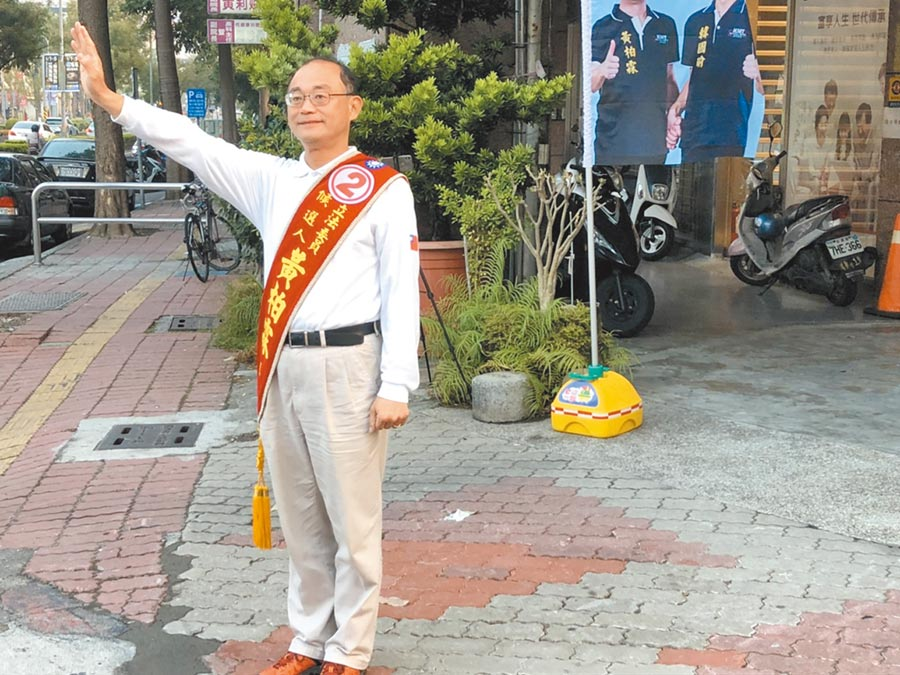 國民黨候選人黃柏霖在高雄市民族路與天祥路的路口拜票,經過路口的車輛絡繹不絕,黃柏霖不停地揮手、鞠躬致意。(洪浩軒攝)