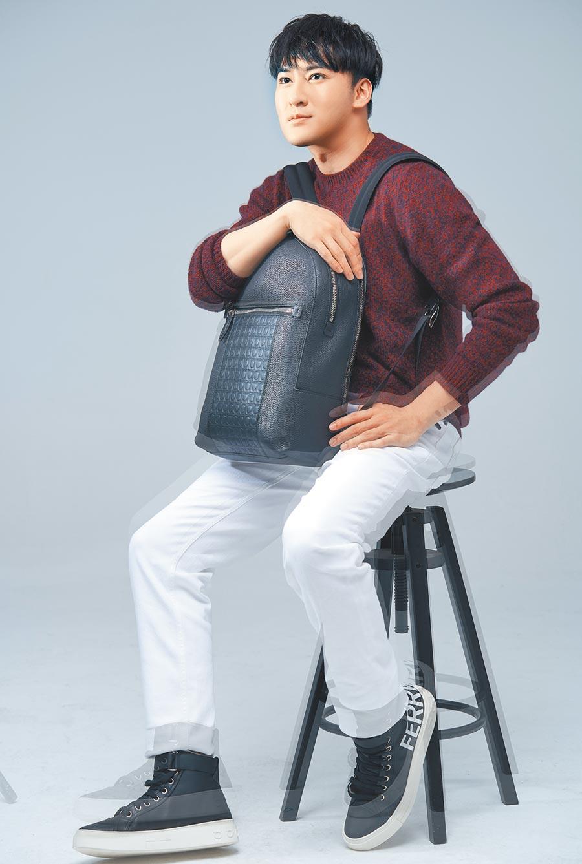 沈建宏喜歡旅遊,想去海島國家好好放鬆。Ferragamo酒紅色毛衣3萬900元,白色長褲1萬6900元,FIRENZE黑色牛皮後背包6萬5900元,AYR黑色牛皮高筒球鞋2萬7900元。(攝影/JOJ PHOTO)