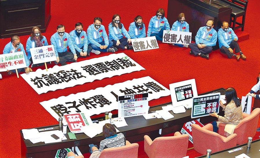 2019年12月31日,立法院院會處理《反滲透法》草案,國民黨立委戴口罩拉布條,在議場內靜坐抗議法案侵害人權(圖上方),民進黨立委則在座位區立起標語表達支持(圖下方)。(本報系資料照片)