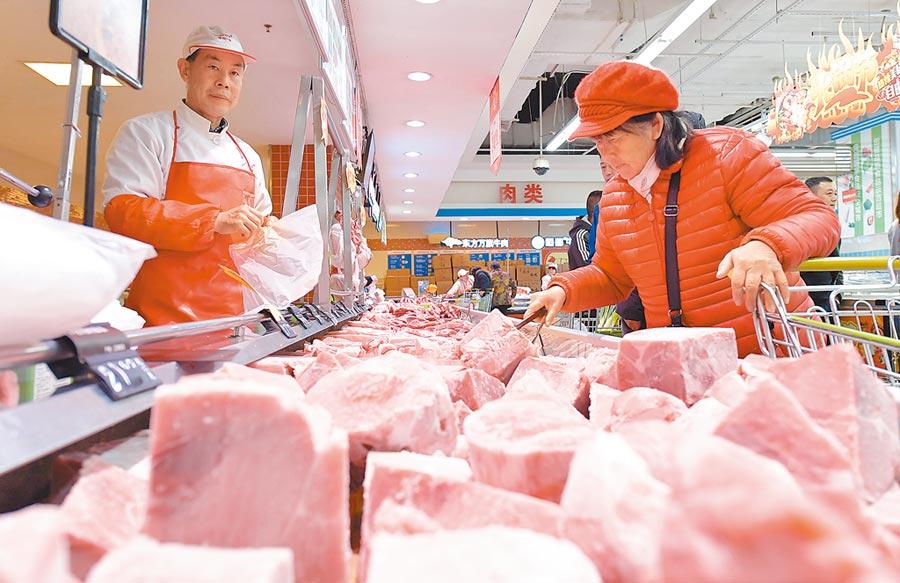 大陸春節期間豬肉市場保供。圖為2019年12月22日,民眾在南昌一家超市選購儲備豬肉。(新華社)