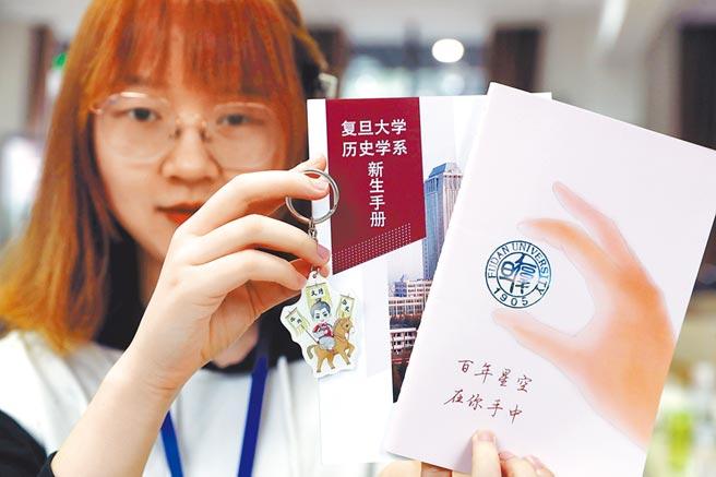 復旦章程修改惹議,凸顯學術自由受限,圖為2019年復旦迎新,一名學生展示新生手冊。(新華社資料照片)