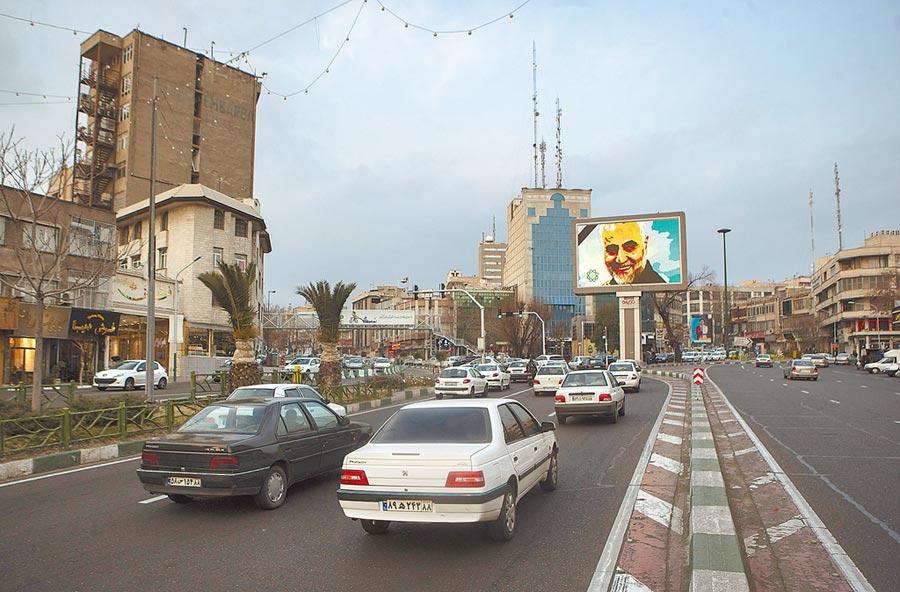 1月3日,伊朗悼念遭美軍襲擊的高級將領卡西姆.蘇萊馬尼,德黑蘭街道上的大螢幕顯示他的頭像。(新華社)