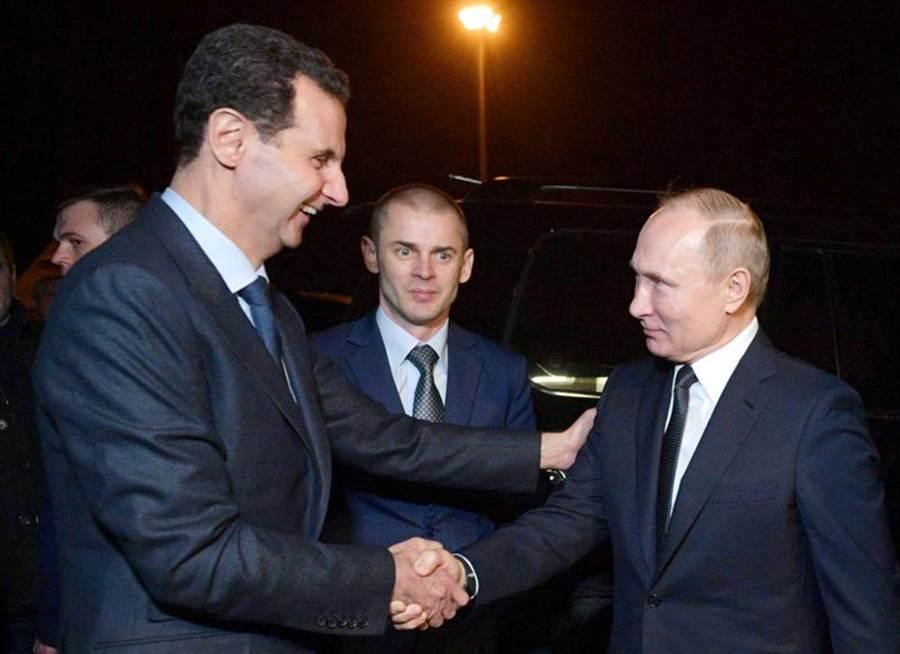 就在伊朗發動報復攻擊不久前,俄羅斯總統普丁(右)意外突訪敘利亞並會見總統阿賽德,格外引人關注。(美聯社)