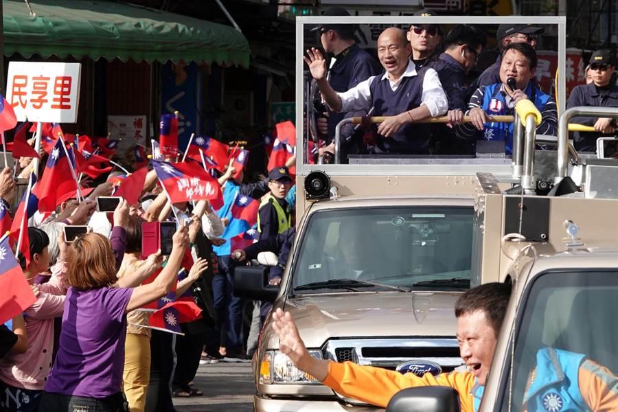 國民黨總統候選人韓國瑜(車上左)5日啟動首場車隊掃街拜票,支持者揮舞國旗夾道歡迎。(資料照,黃世麒攝)