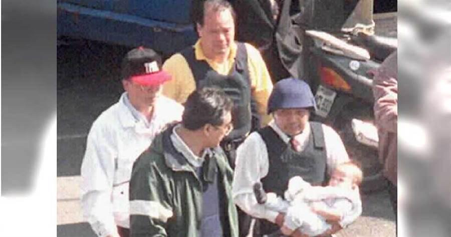 時任台北市刑警大隊長的侯友宜,接著戴鋼盔進入南非武官卓懋祺家中救出小嬰兒。(圖∕報系資料照)