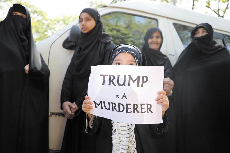 美伊衝突一觸即發,圖為舉抗議牌的小女孩。(路透)
