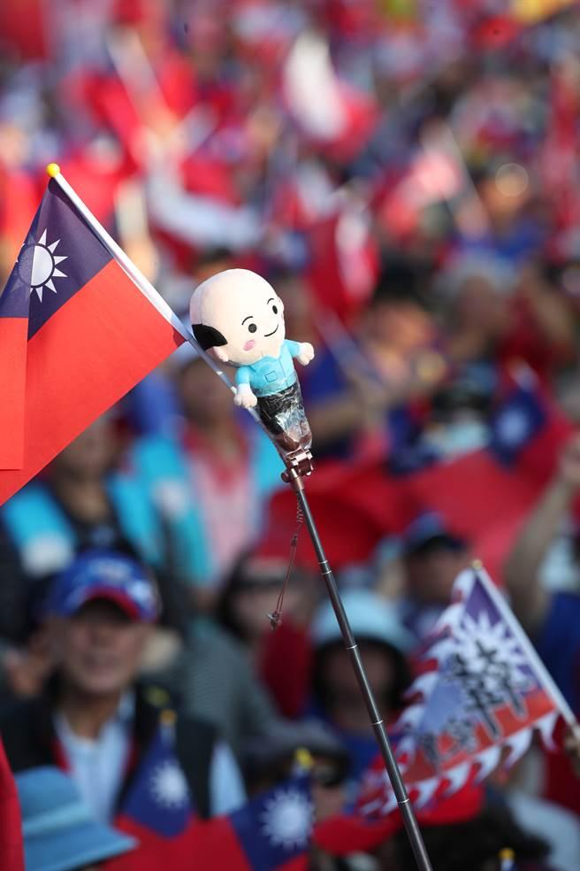 國民黨9日在總統府前的凱達格蘭大道舉辦「台灣安全,人民有錢」凱道勝利晚會,太陽未下山現場即擠滿了熱情的民眾,一同力挺韓國瑜。一個韓國瑜的人偶國旗一同在人群中搖晃。(鄭任南攝)