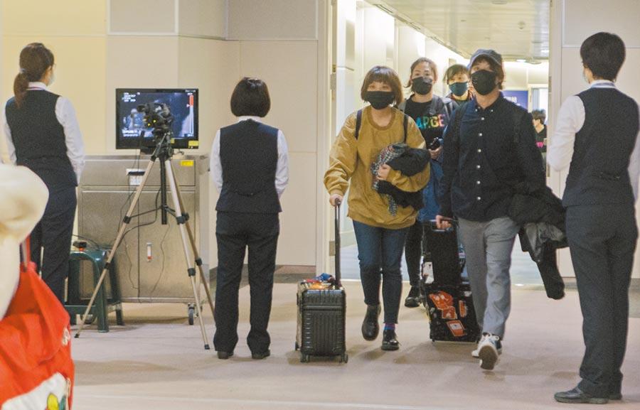 武漢不明肺炎延燒,疾管署決將其列為法定傳染病。圖為1月2日,武漢直航桃園班機旅客一出登機門,即做發燒篩檢。(本報系資料照片)