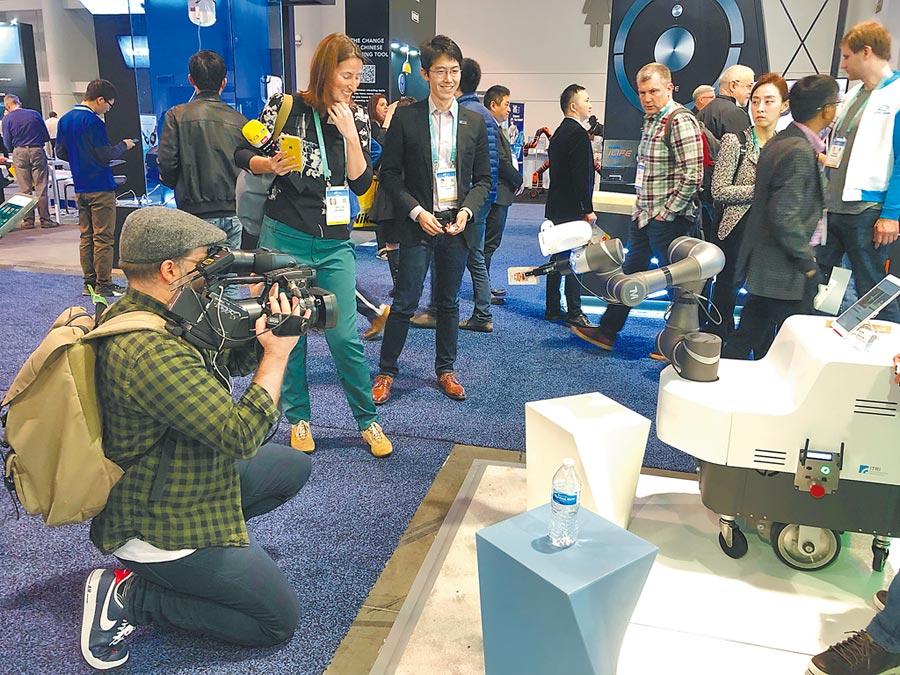 工研院「行動手臂式機器人系統」在CES現場送小禮物給參觀者,獲得佳評。(工研院提供/王玉樹台北傳真)