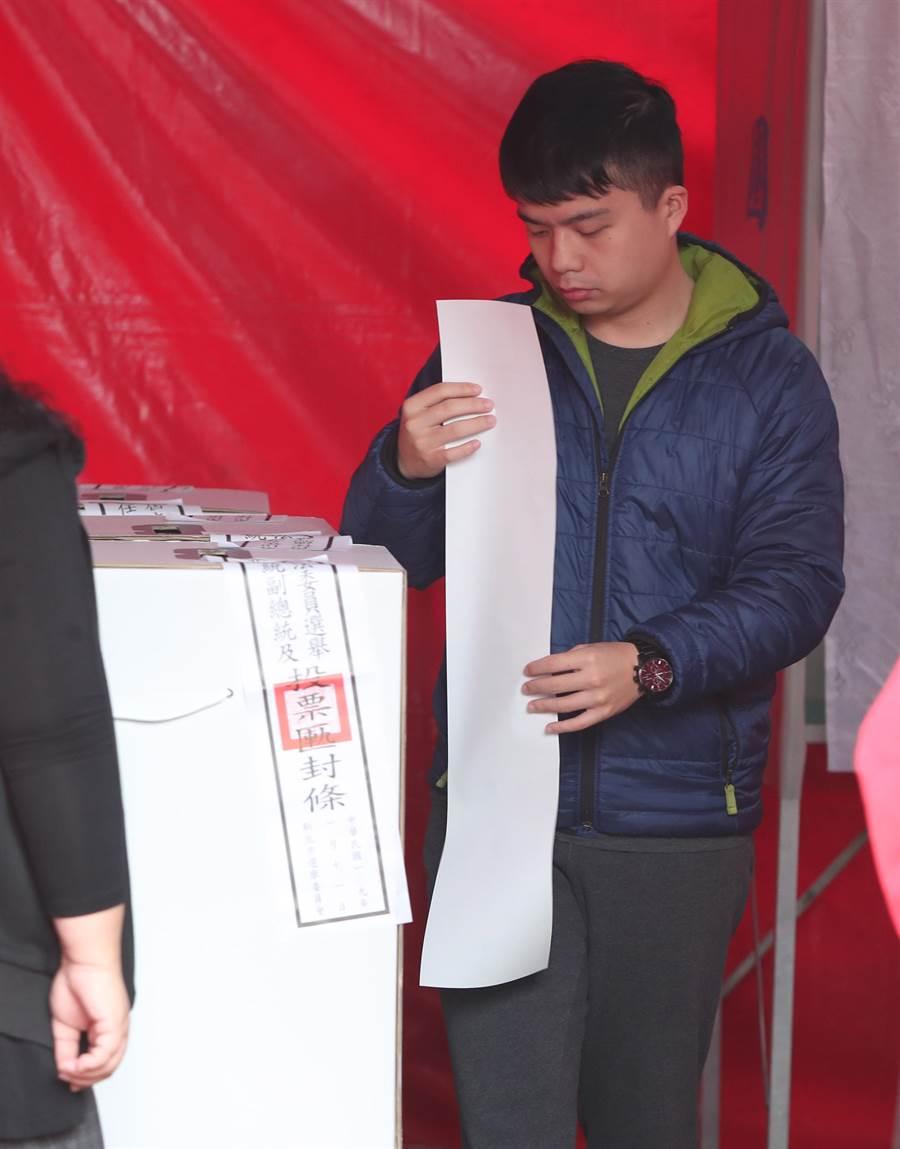 在新北汐止的一處由投票所,一位年輕人進行投票,將超長的政黨票折疊後投入票箱。(鄭任南攝)