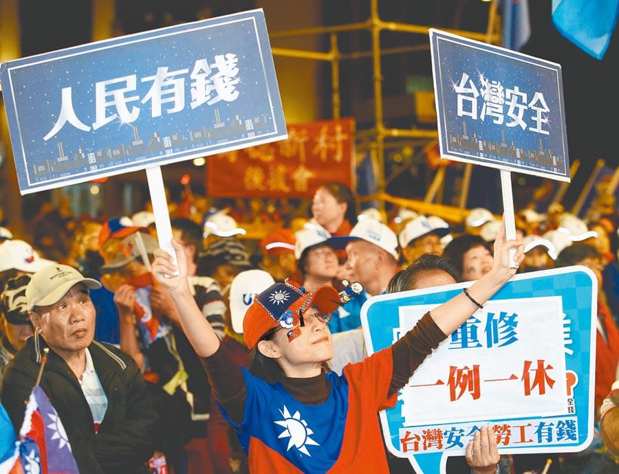 新北選前之夜造勢10日登場,熱情支持者搖動「人民有錢、台灣安全」的紙牌支持韓國瑜的政見。(陳怡誠攝)