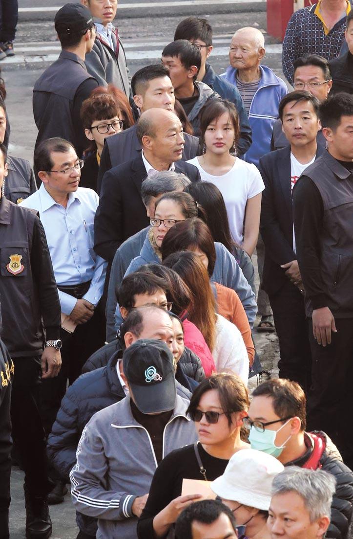 國民黨總統候選人韓國瑜(中後)11日在女兒韓冰陪同下前往投票所,跟著民眾一同排隊,投下本屆大選的神聖一票。(陳信翰攝)