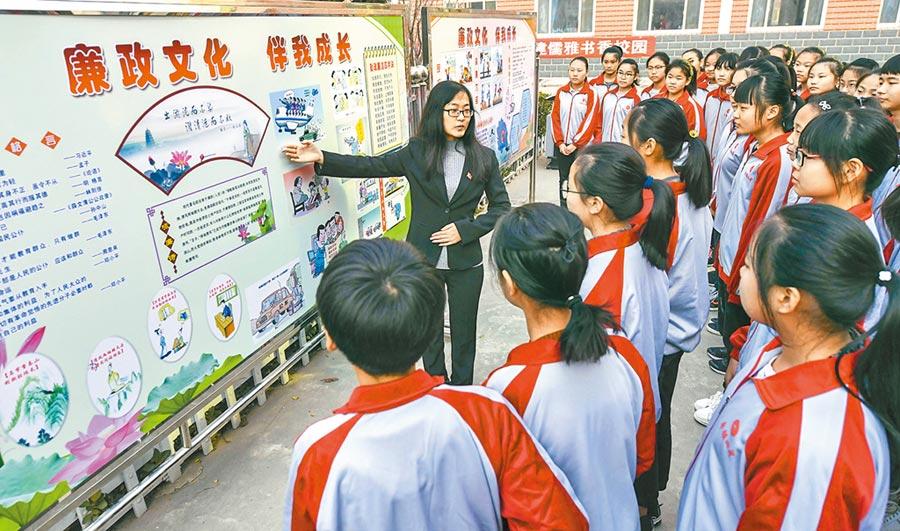 中共中央巡視組向國台辦提出意見,其中包括防範廉政風險不夠到位等問題,圖為河北一紀委幹部向學生講解廉政文化。(新華社資料照片)