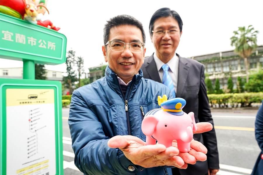 宜蘭市的幾米站牌今天正式啟用,市長江聰淵展示打卡拍照抽獎的獎品幾米幸福小象存錢筒。(李忠一攝)