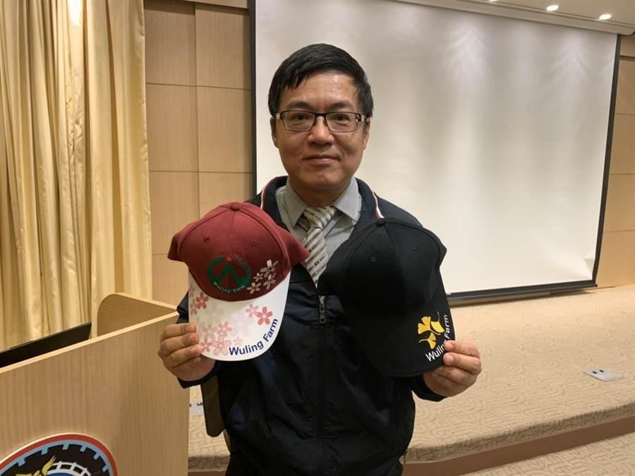 武陵農場副場長胡發韜手拿2頂文青特色帽。(潘千詩攝影)