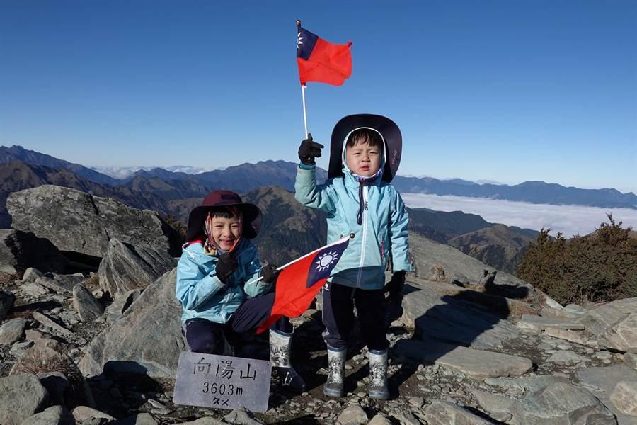 元旦連假,7歲的阿興與5歲的阿賢登上海拔3603向陽山,開心揮舞國旗 。(邱德鑫提供/莊哲權台東傳真 )