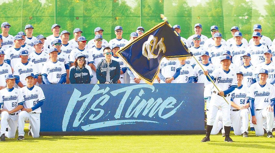 富邦悍將昨開訓,總教練洪一中(前右)從領隊蔡承儒手中接下隊旗揮舞,球團並宣布新球季口號「It's Time」。(中央社)