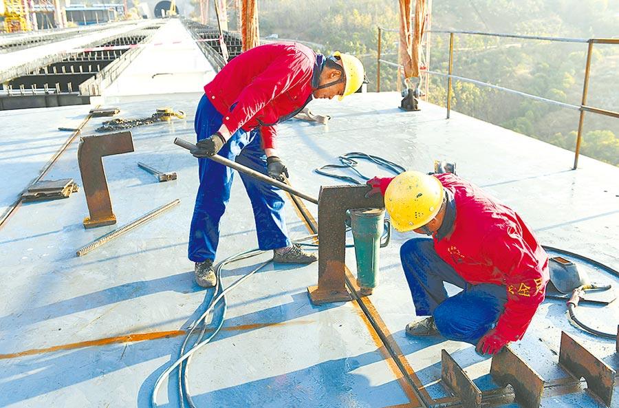 2019年12月30日,工作人員在雲南大瑞鐵路怒江特大橋上進行鋼箱梁調平作業。(新華社)