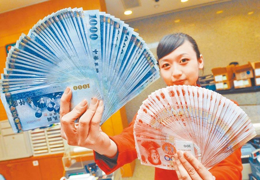 中央銀行放手讓新台幣重返29字頭。圖為銀行員工展示新台幣與人民幣。(本報系資料照片)