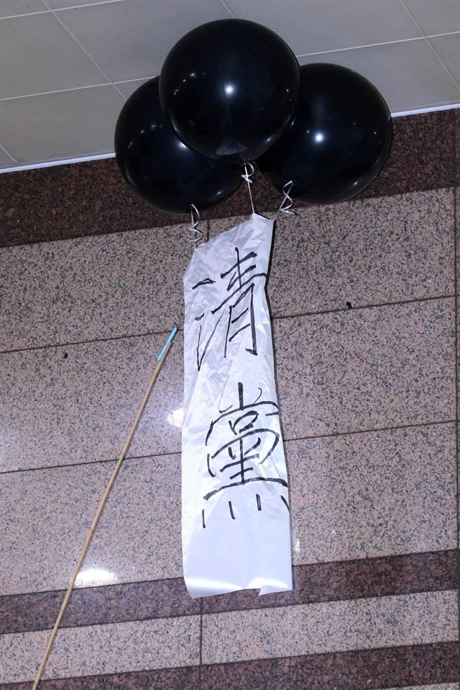 青年軍混入黨部大樓直搗會議室外抗議,留下綁有「清黨」白布條的氣球高懸在大廳天花板,黨工用長竿將氣球搓破後取下。(黃世麒攝)