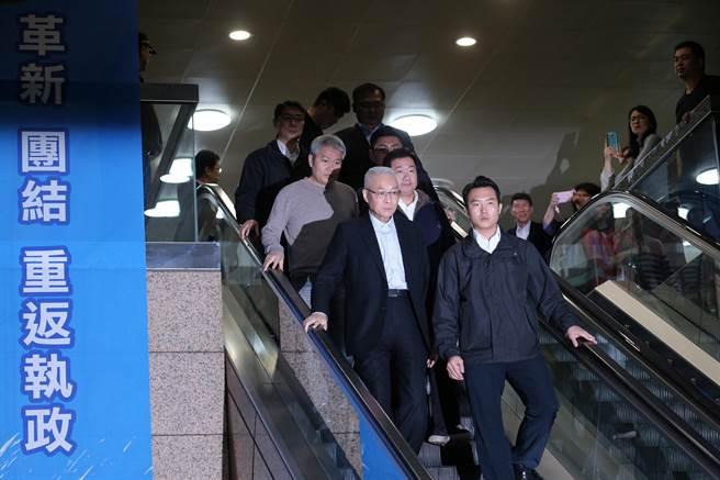 黨主席吳敦義(前排左)為敗選負責請辭下台,黨務一級主管也全數去職;中常會結束後,吳敦義走下樓,落寞的神情與一旁的激烈布條形成強烈對比。(黃世麒攝)