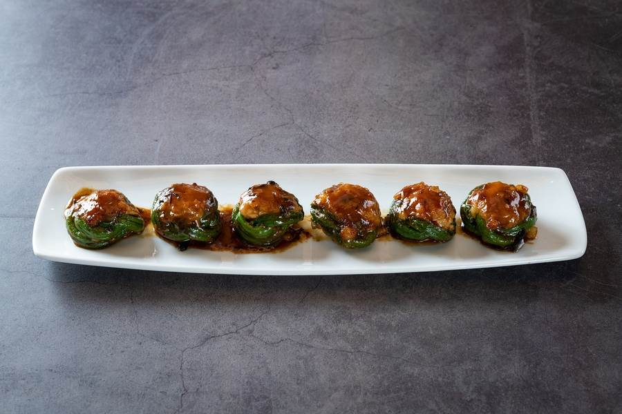 「順德釀豆角」將長豆煮軟冰鎮手工打結後,填入豬肉蓉與河蝦泥的釀料,並以欖菜點睛。(十二粵提供)