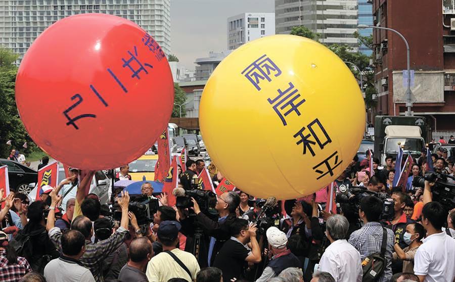 群眾在街頭遊行中滾動《九二共識》及《兩岸和平》大氣球。(王爵暐攝)