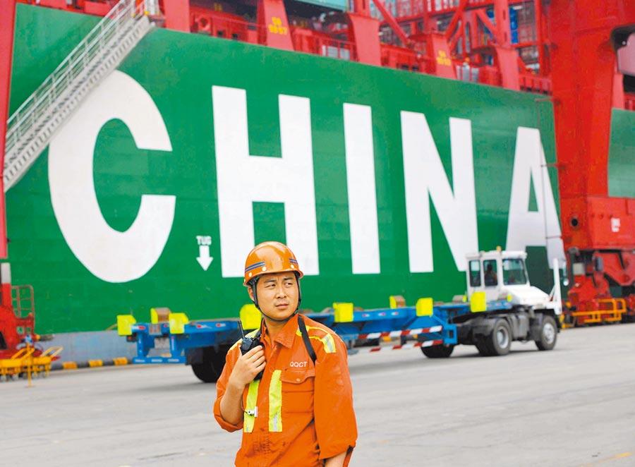 山東青島港外貿貨櫃碼頭,工人指揮貨櫃裝卸。(新華社資料照片)