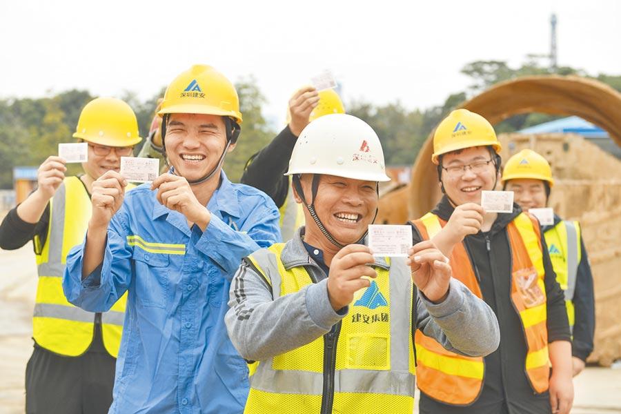 春運是一場涉及30億人次的遷徙潮,圖為務工人員展示春運返鄉火車票。(新華社資料照片)