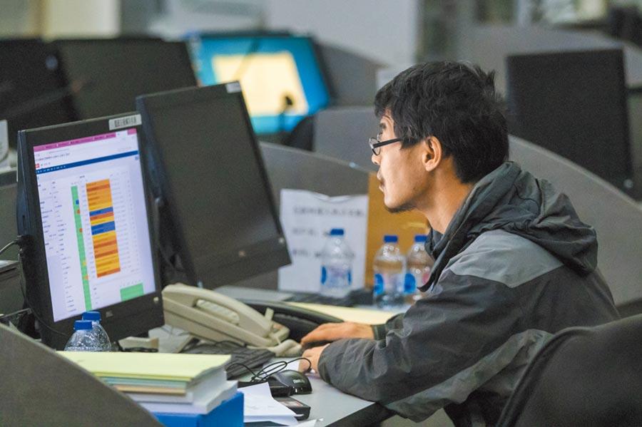 12306網站的工作人員正緊盯電腦螢幕,確定春運鐵路購票順暢。(中新社)