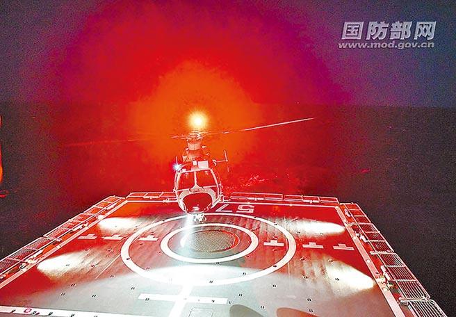運城艦艦載直升機夜間緊急起飛,前出引導艦艇對目標實施打擊。(穆瑞林攝)