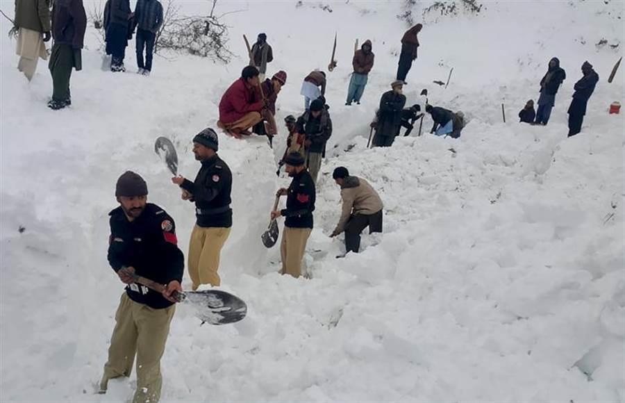 與時間賽跑!巴基斯坦救援人員挖掘厚厚積雪,希望儘快救出受困雪堆中的失蹤人口。(美聯社)