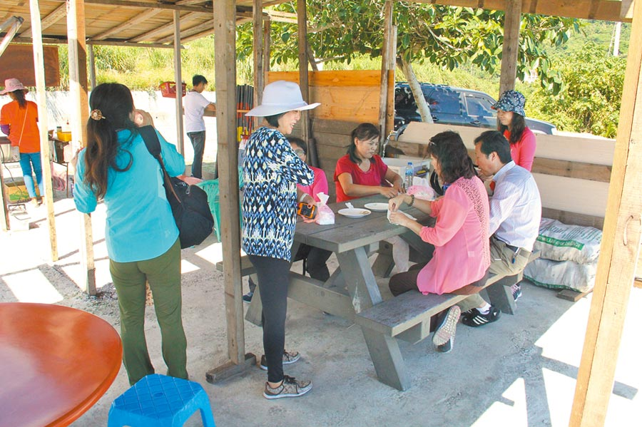 2019年10月8日,自由行陸客在花蓮海岸路邊攤吃烤飛魚。(本報資料照片)