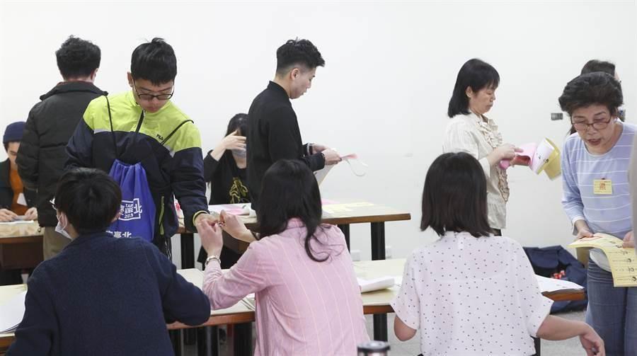 11日舉行總統大選,全球媒體關注。圖為台北市北投福星宮投開票所內,選務人員核對民眾證件。(資料照片,張鎧乙攝)