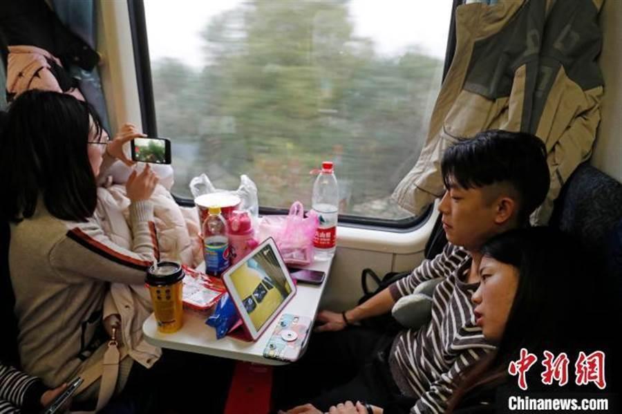 刷微信、上抖音、看新聞 陸春運「慢火車」上不再寂寞。(照片取自中新網)