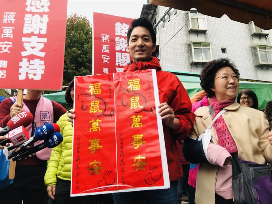 國民黨立委蔣萬安19日上午到北市草埔市場謝票、發放春聯。(張穎齊攝)