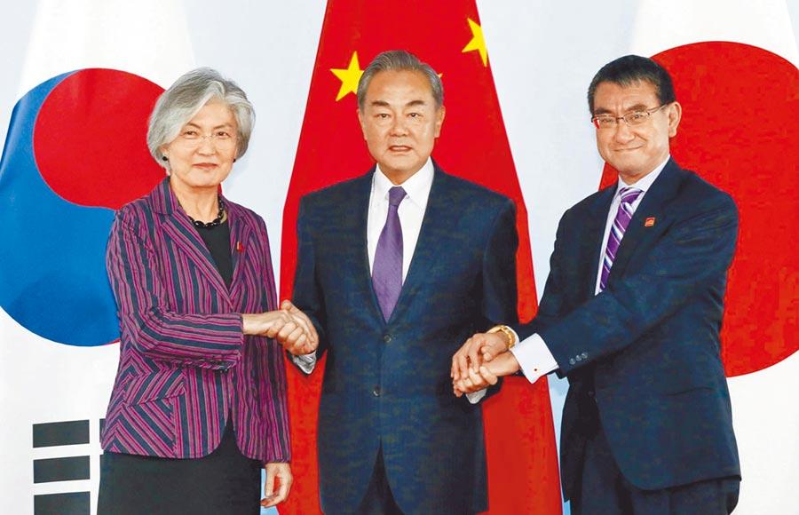 大陸外長王毅(中)與韓國外長康京和(左)、日本外相河野太郎合影。(中新社資料照片)