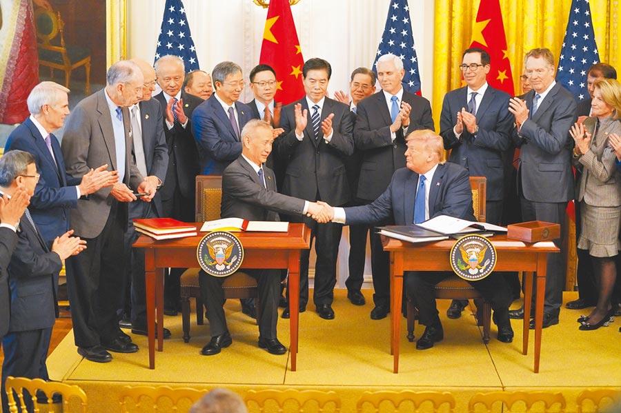 今年因中美貿易戰降溫,有利於資金派對重啟。圖為美國總統川普與大陸國務院副總理劉鶴在華盛頓簽署中美第一階段貿易協議的畫面。(新華社)