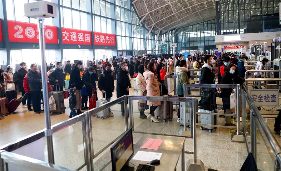 圖中為21日武漢火車站大廳內以紅外體溫檢測儀檢測進出旅客體溫。(圖/中新社)