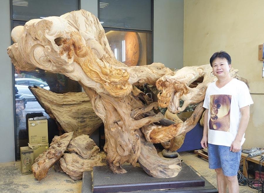 木雕藝術家官小欽和他的龍雕創作「傳承」合影。圖/黃俊榮