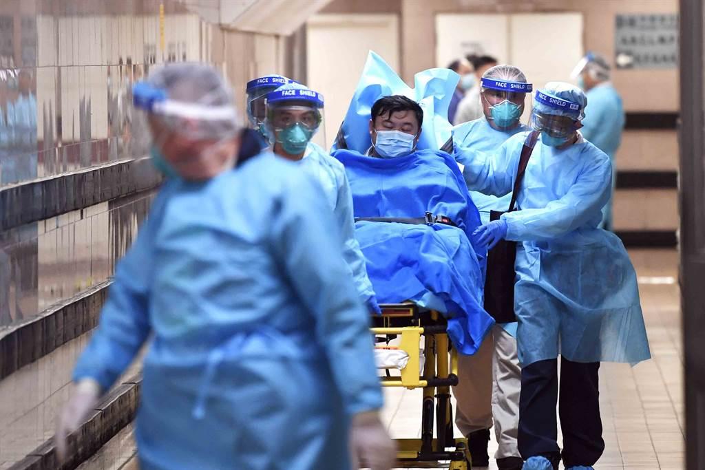 醫護人員護送香港首宗高度懷疑並已初步確診感染新型冠狀病毒肺炎的男性患者離開伊利沙伯醫院,由救護車轉送至其他醫院。(圖/中新社)