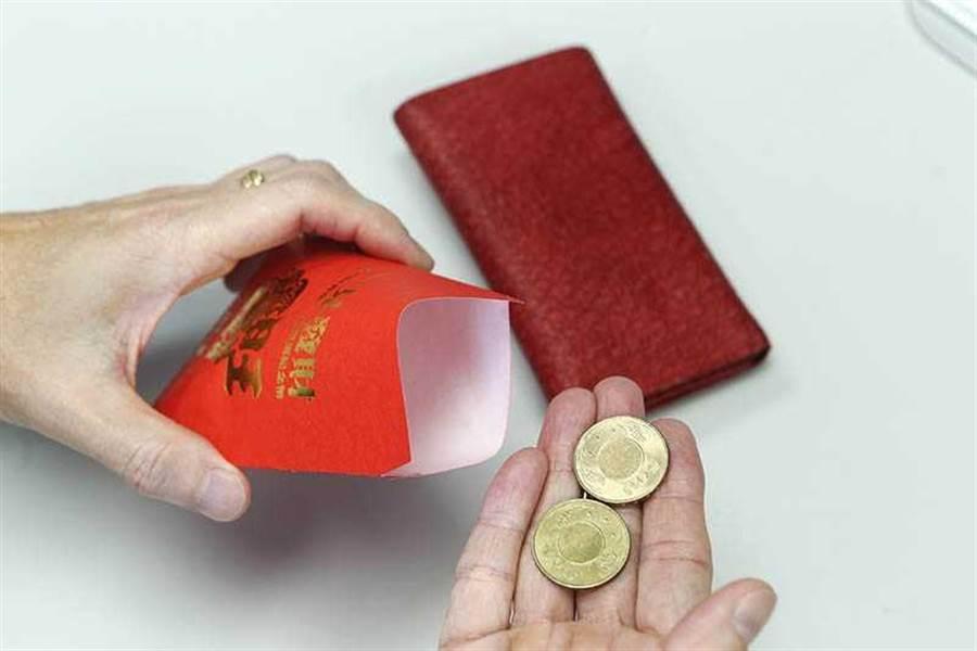 將兩個50元銅板放入紅包袋中,再放入皮夾或包包,可以招財。(圖/李宗明攝)