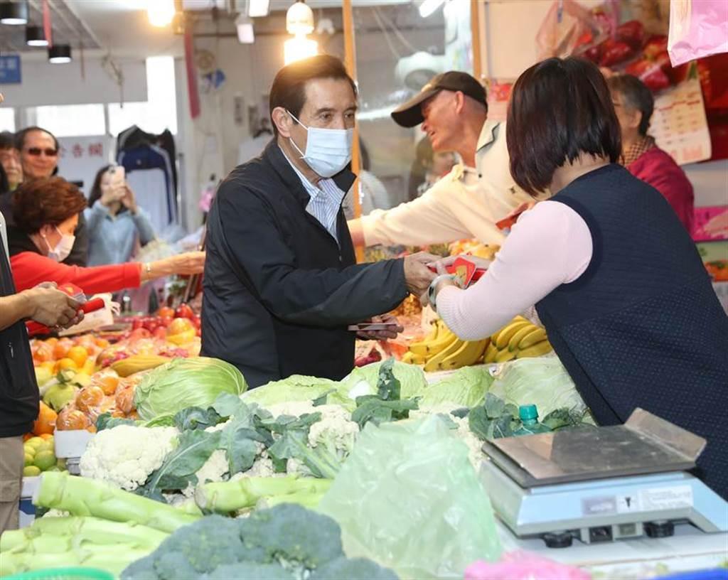戴著ロ罩的前總統馬英九(中)23日前往興隆市場,發送春聯、福卡給買年菜的民眾及攤商。(資料照,劉宗龍攝)