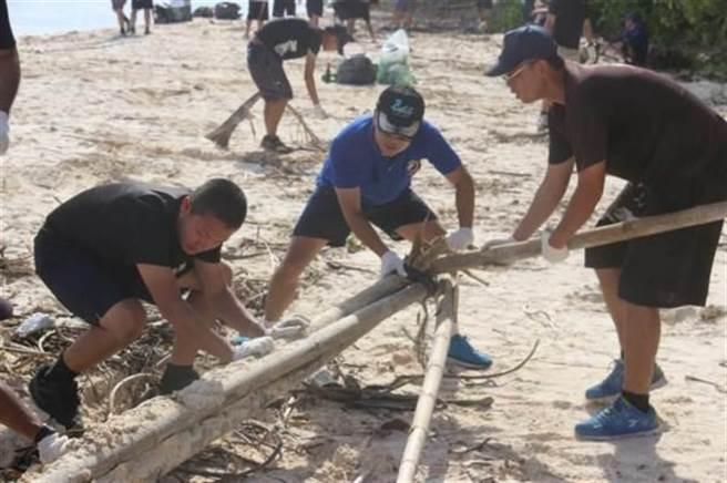 頂著烈日冒著汗水,太平島上的海巡官兵以淨灘活動過新年。(海巡署提供)