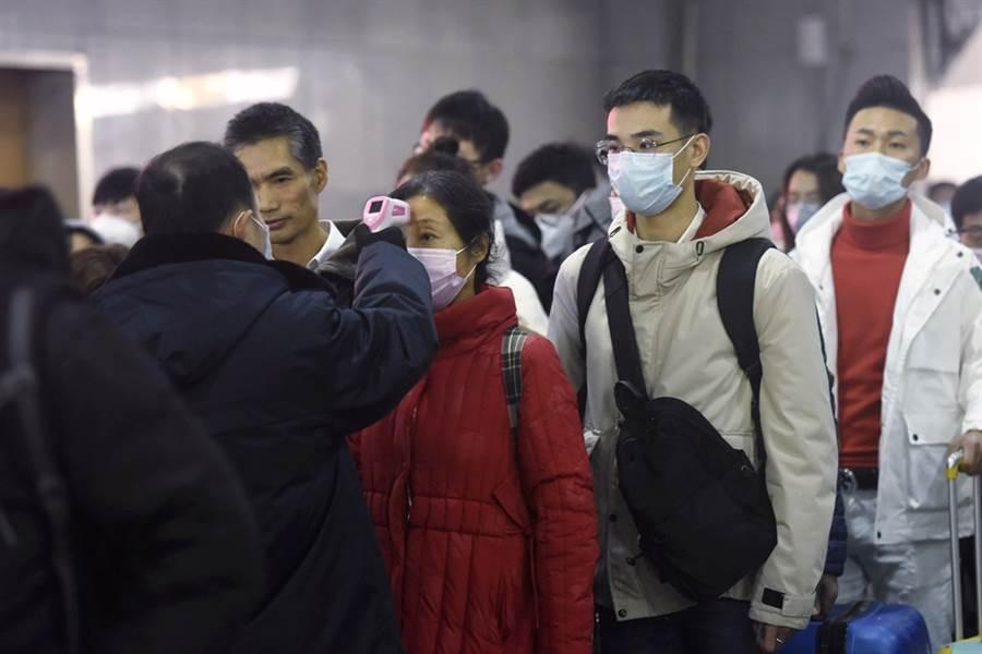 武漢肺炎疫情擴大,杭州火車站的乘客紛紛戴口罩量溫度。(美聯社)
