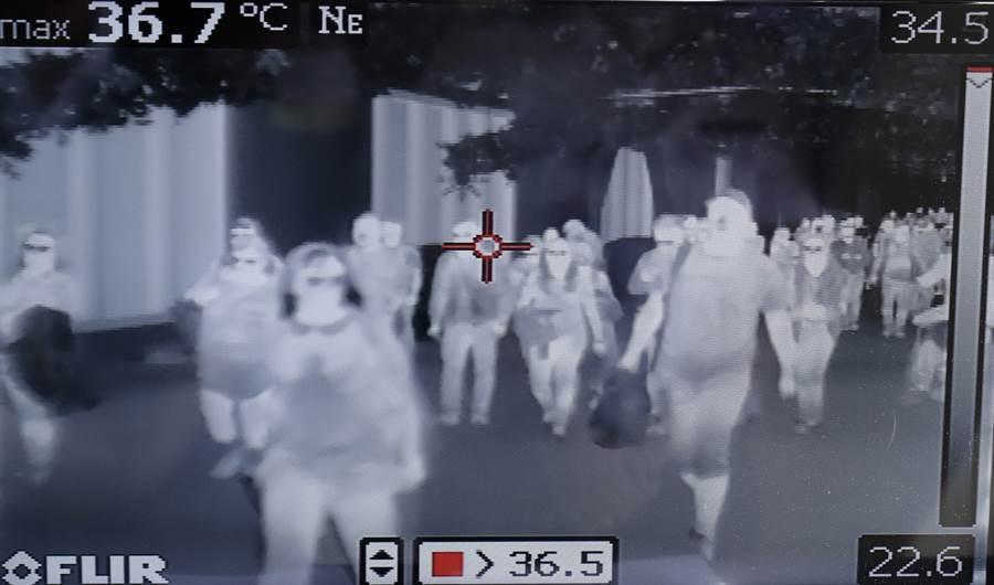 旅客23日抵達菲律賓馬尼拉國際機場,當局用熱掃描器檢疫的畫面。(美聯社)