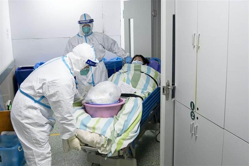 大陸醫護人員將感染武漢肺炎的病人轉移出重症病房。(新華社)