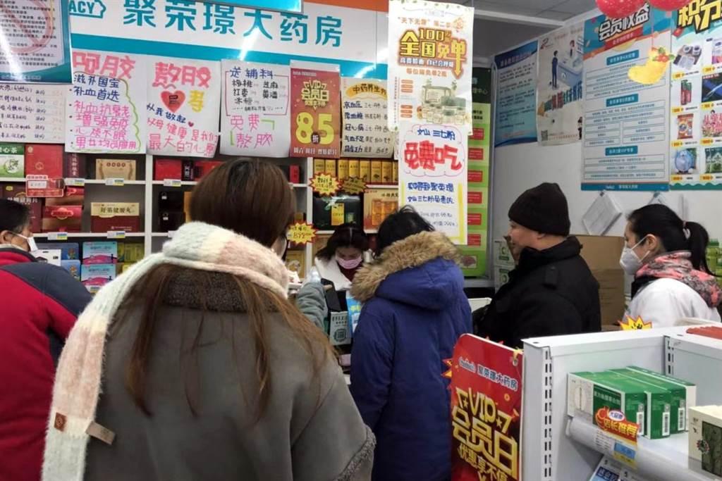 武漢市民在一家藥店排隊購買口罩等防護用品的畫面。(中新社)