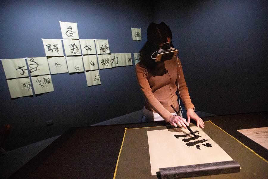 「2020高雄獎」優選獎作品「鏡像之書」,藝術家柯良志打造,民眾可現場體驗腦手不協調的書寫感受。(袁庭堯攝)